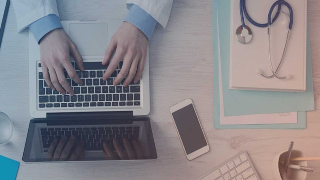Schreibtisch eines Arztes mit Laptop