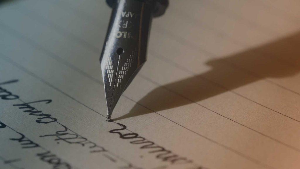 Person schreibt einen Brief mit Füller