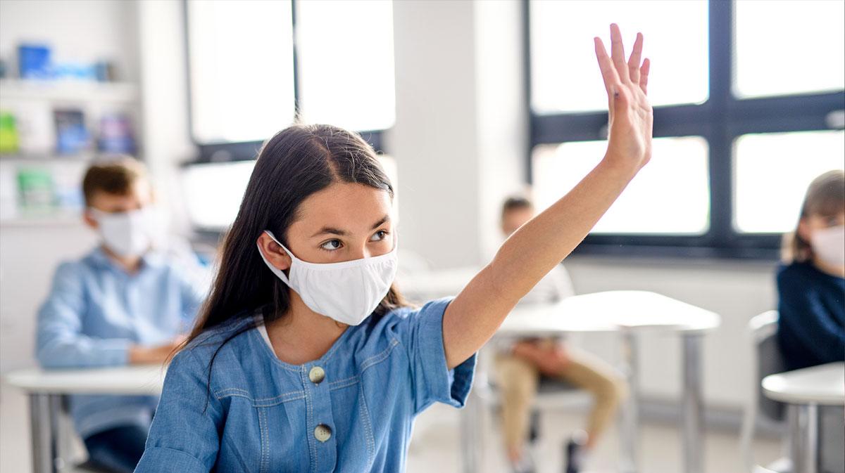 Schulkind mit Maske im Unterricht