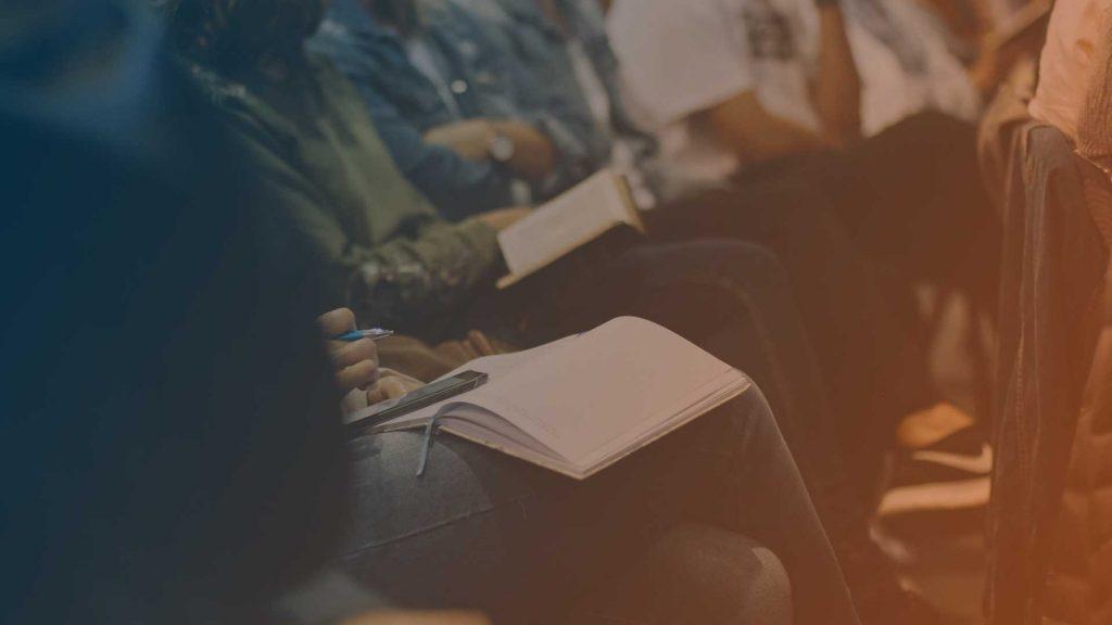 Teilnehmer machen Notizen bei einem Selbsthilfegruppentreffen