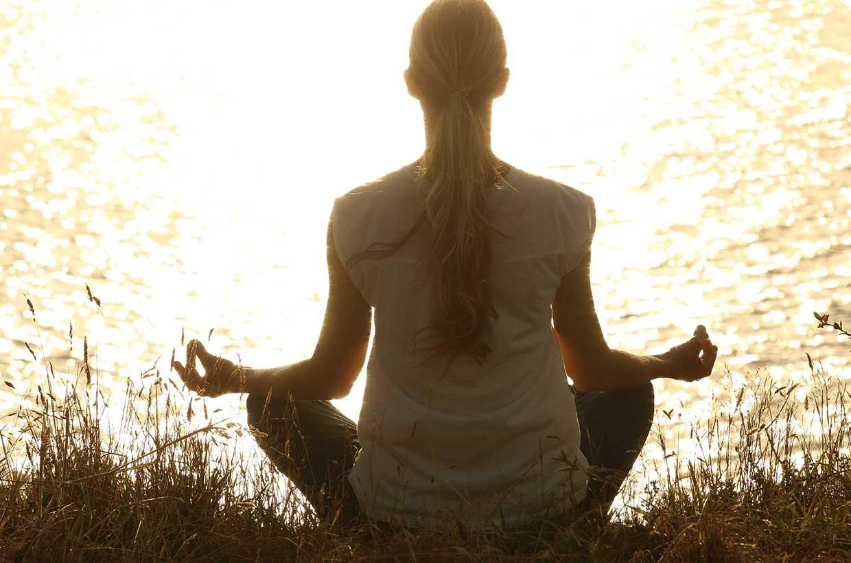 Frau macht Yoga am See um zu Entspannen.